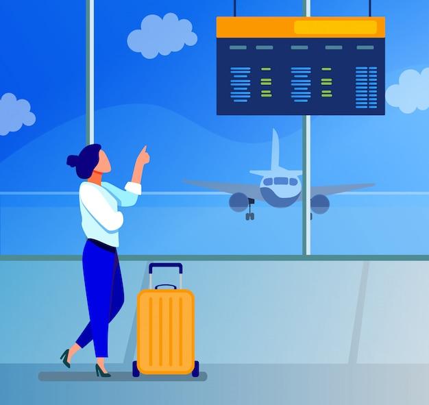 Digitales board der abflugberatung der frau im flughafen