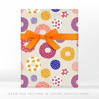 Donut-kuchen mit topping- oder frosting-verpackung oder geschenkpapier. geschenkbox mit band