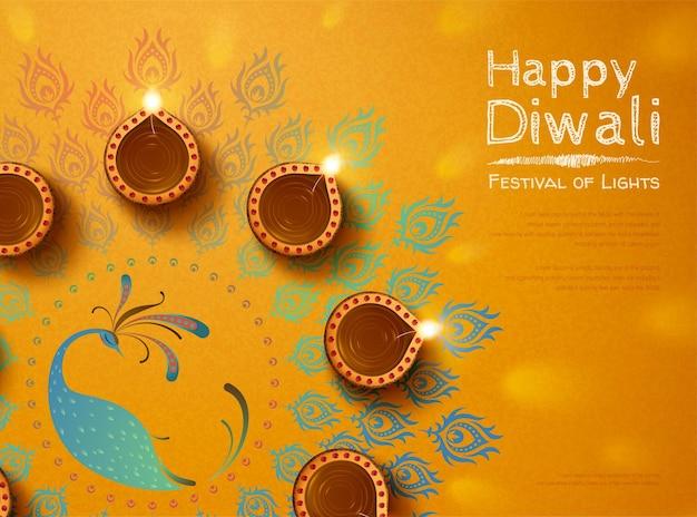 Draufsicht des diwali-designs mit öllampen und pfau-rangoli auf chromgelbem hintergrund