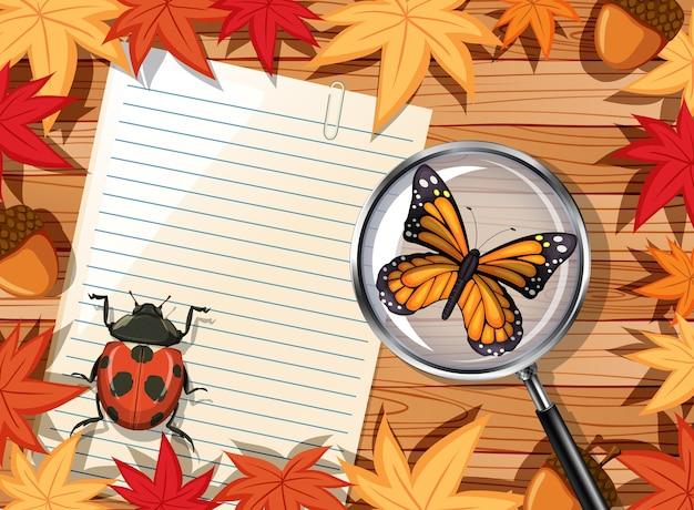 Draufsicht des holztischs mit leerem papier und insekten- und herbstlaubelement