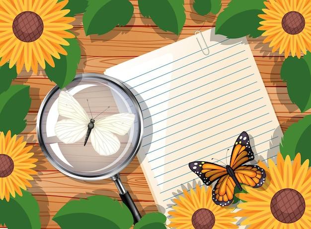 Draufsicht des leeren papiers auf tisch mit blättern und sonnenblumenelementen