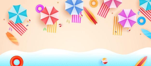 Draufsicht strandhintergrund mit regenschirmen, bällen, schwimmring, sonnenbrille, surfbrett, sandalen, seestern und meer. luftaufnahme des sommerstrandes.