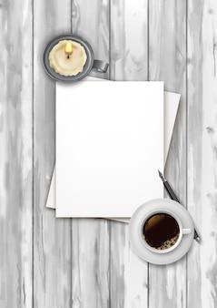 Draufsichthintergrund mit einem leeren blatt papier, kaffeetasse, stift und kerze auf einem hölzernen hintergrund