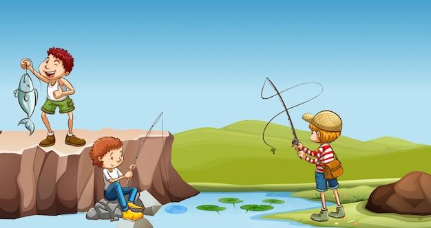 Drei jungen, die am fluss fischen
