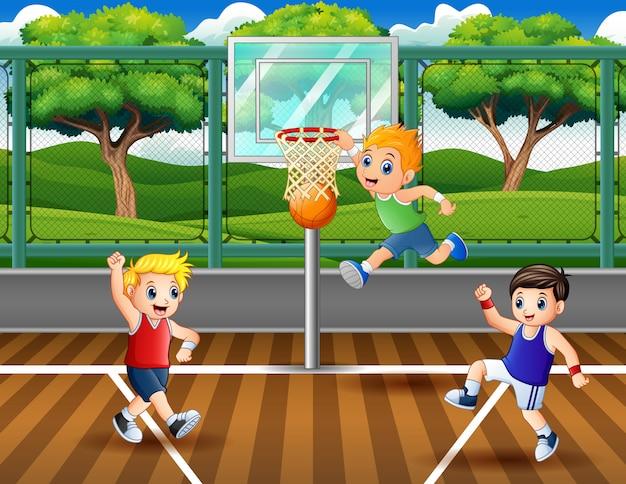Drei jungen, die am gericht basketball spielen
