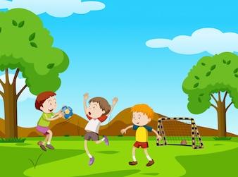 Drei Jungen, die Ball im Park spielen