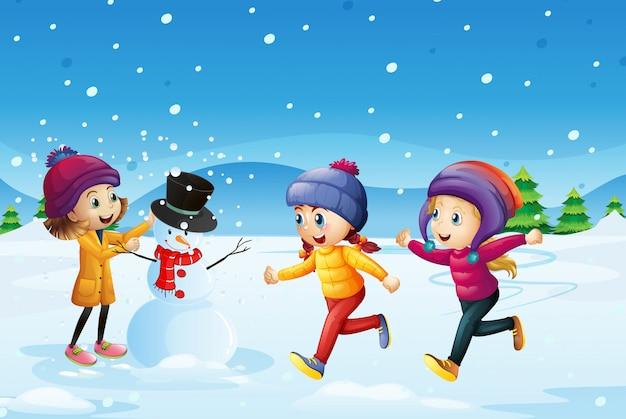 Drei kinder, die schneemann auf dem schneegebiet spielen