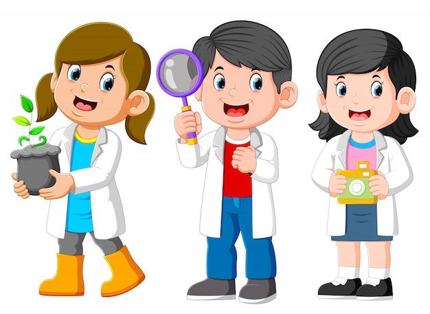 Drei kinderwissenschaftler-tragendes weißes laborkleid und halten eines sämlings, lupe, kamera