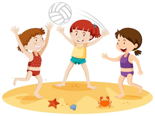 Drei mädchen, die mit einem ball am strand spielen