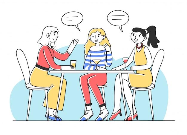Drei mädchen sitzen am tisch im café und reden