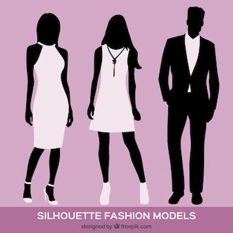 Drei silhouetten der mode-modelle auf violettem hintergrund