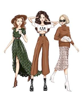 Drei stilvolle frauen in trendiger outfits