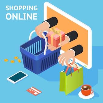 E-commerce- oder online-einkaufskonzept mit händen, die aus einem computerbildschirm herausgreifen und eine einkaufstasche und einen korb mit einem geschenk und einer kreditkarte und einem tablet halten, die daneben liegen
