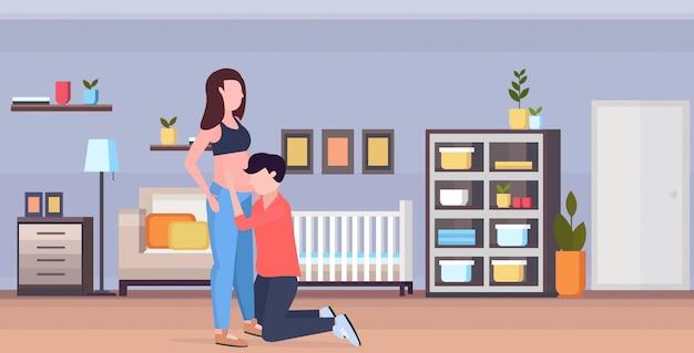 Ehemann auf dem knie hört dem bauch seiner schwangeren frau fröhliche familie zu, die neugeborenenbabyschwangerschafts-elternschaftskonzept des modernen kinderschlafzimmers innen horizontal in voller länge wartet