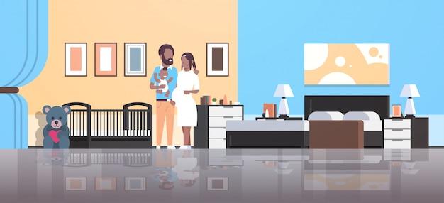 Ehemann mit schwangerschaftsfrau, die neugeborenen kleinen sohn hält, der nahe krippe glücklicher familienelternschaft steht