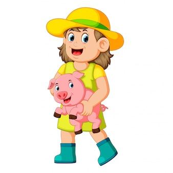 Ein bauernmädchen, das ein schwein hält