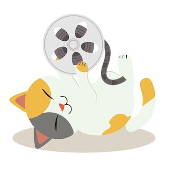 Ein charakter der netten katze schlafend aus den grund. katze spielt mit movie film tape und es ist so glücklich. eine süße katze im flachen vektor-stil
