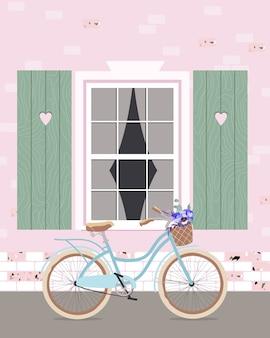 Ein fahrrad an eine wand gelehnt. himmelblaues fahrrad unter dem fenster. moderne romantische illustration eines fahrrads mit blumen in einem korb, der vor einem fenster steht. blick auf das alte gemütliche haus im freien.
