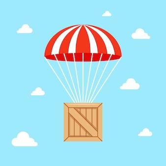 Ein fallschirm mit einer holzkiste fällt zu boden.