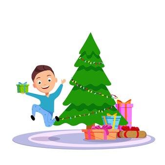 Ein fröhlicher junge erhielt ein geschenk zu weihnachten. springen mit glück neben dem weihnachtsbaum.
