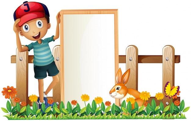 Ein junge, der eine gestaltete leere fahne mit einem kaninchen hält