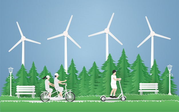 Ein junge, der einen elektroroller fährt, paar, das mit dem fahrrad in den park auf dem grünen gras im parkhintergrund reist.