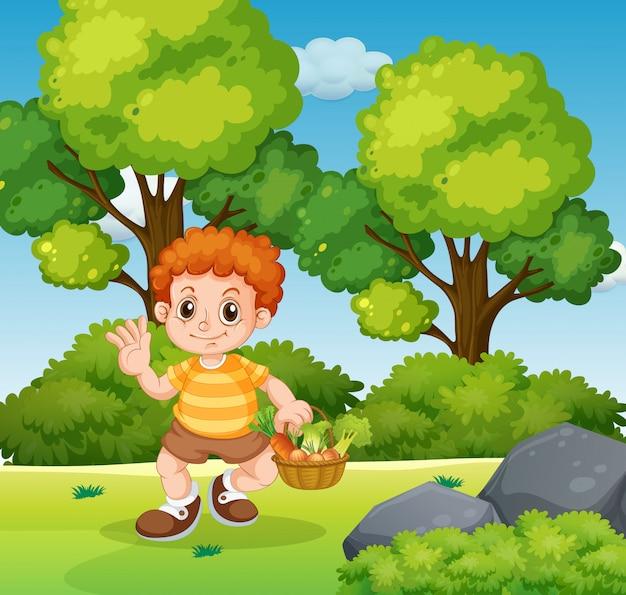 Ein junge, der gemüsekorb im park hält