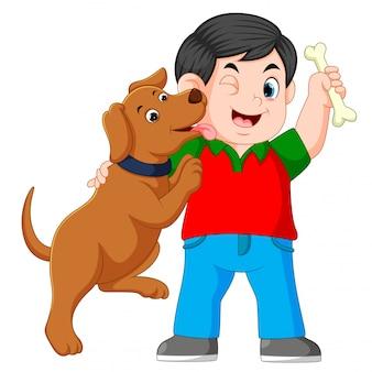Ein junge, der knochen mit seinem hund hält
