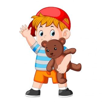 Ein junge, lustiges spiel mit dem teddybären