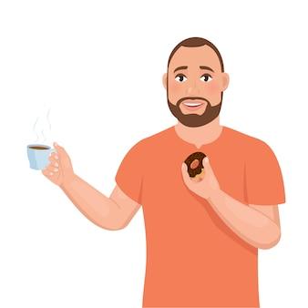 Ein junger bärtiger mann hält eine tasse kaffee in der einen und einen donut in der anderen hand.