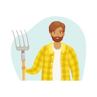 Ein junger männlicher bauer in einem karierten hemd mit einem heuhaufen in den händen. die jahreszeit der ernte. getreideanbau und tierhaltung. subsistenzwirtschaft.
