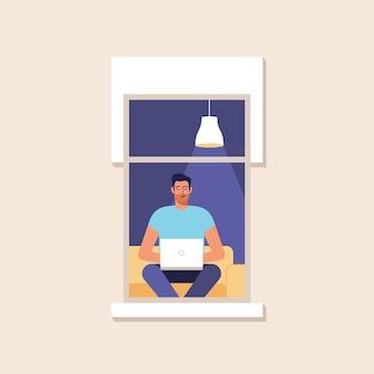 Ein junger mann arbeitet zu hause am computer. zuhause arbeiten. online-studium, bildung. fassade des hauses mit einem fenster.