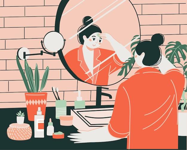 Ein junges süßes mädchen vor einem spiegel im badezimmer reinigt und befeuchtet ihre haut