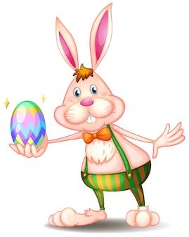 Ein kaninchen, das ein osterei hält