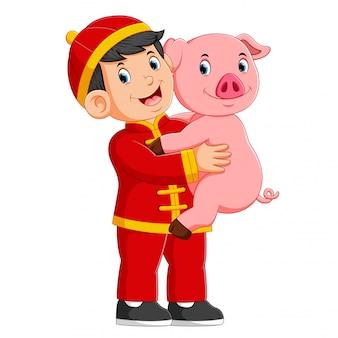 Ein kleiner junge spielt im chinesischen neuen jahr mit einem schwein