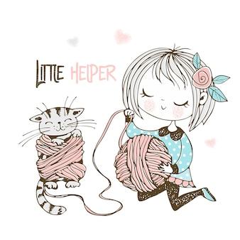 Ein kleines süßes mädchen wickelt garn in eine kugel und das kätzchen verwickelt sich in den fäden.