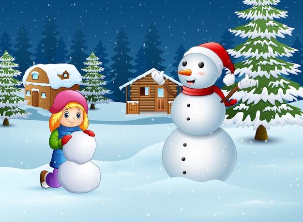 Ein mädchen, das schneemann im winter und in der schneebedeckten landschaft macht