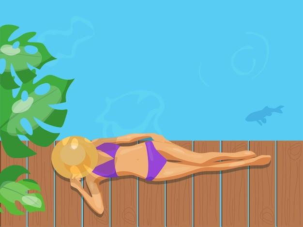 Ein mädchen in badeanzug und hut liegt auf einer brücke am blauen meer sommerferien