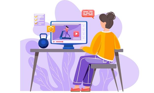 Ein mädchen sitzt mit einem laptop und einer kettlebell an einem tisch.