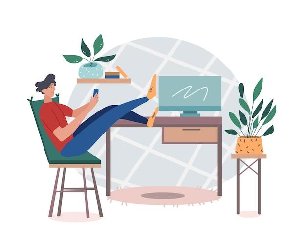 Ein männlicher student oder freiberuflicher arbeiter, der zu hause sitzt und das telefon scrollt und ihre füße mit einem computer auf den tisch legt.