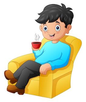 Ein mann, der auf dem sofa sitzt, während er eine tasse heißen kaffee hält