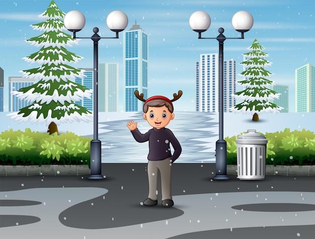 Ein mann, der hand auf winterpark lächelt und wellenartig bewegt