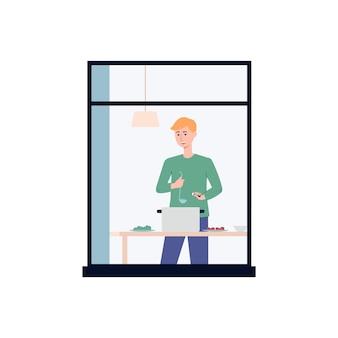 Ein mann, der im fenster der küche zu sehen ist und essen zubereitet. der häuslichen aktivität während der isolation, quarantäne, wochenende oder urlaub.