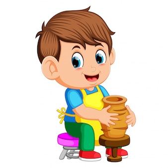 Ein mann, der in einer töpferwerkstatt eine tonvase auf einer töpferscheibe formt