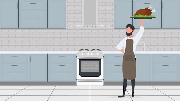 Ein mann hält einen truthahnbraten in der hand. der typ in der küchenschürze hält brathähnchen in der hand.