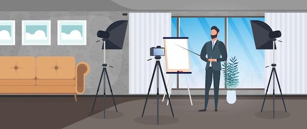 Ein mann im anzug mit krawatte hält eine präsentation vor der kamera. der lehrer schreibt eine lektion. das konzept des bloggens, online-schulungen und konferenzen. kamera auf stativ, softbox.