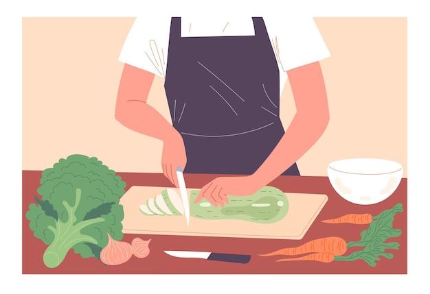 Ein mann schneidet gemüse bei der zubereitung einer mahlzeit