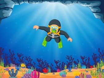 Ein Mann taucht mit der gelben Schwimmbrille unter dem blauen Meer