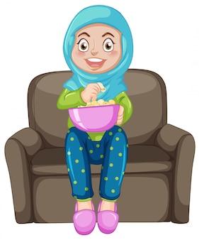 Ein moslemisches mädchen, das popcorn isst