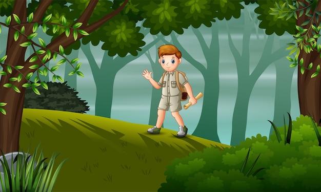 Ein pfadfinderjunge, der auf dem hügel mit karten wandert
